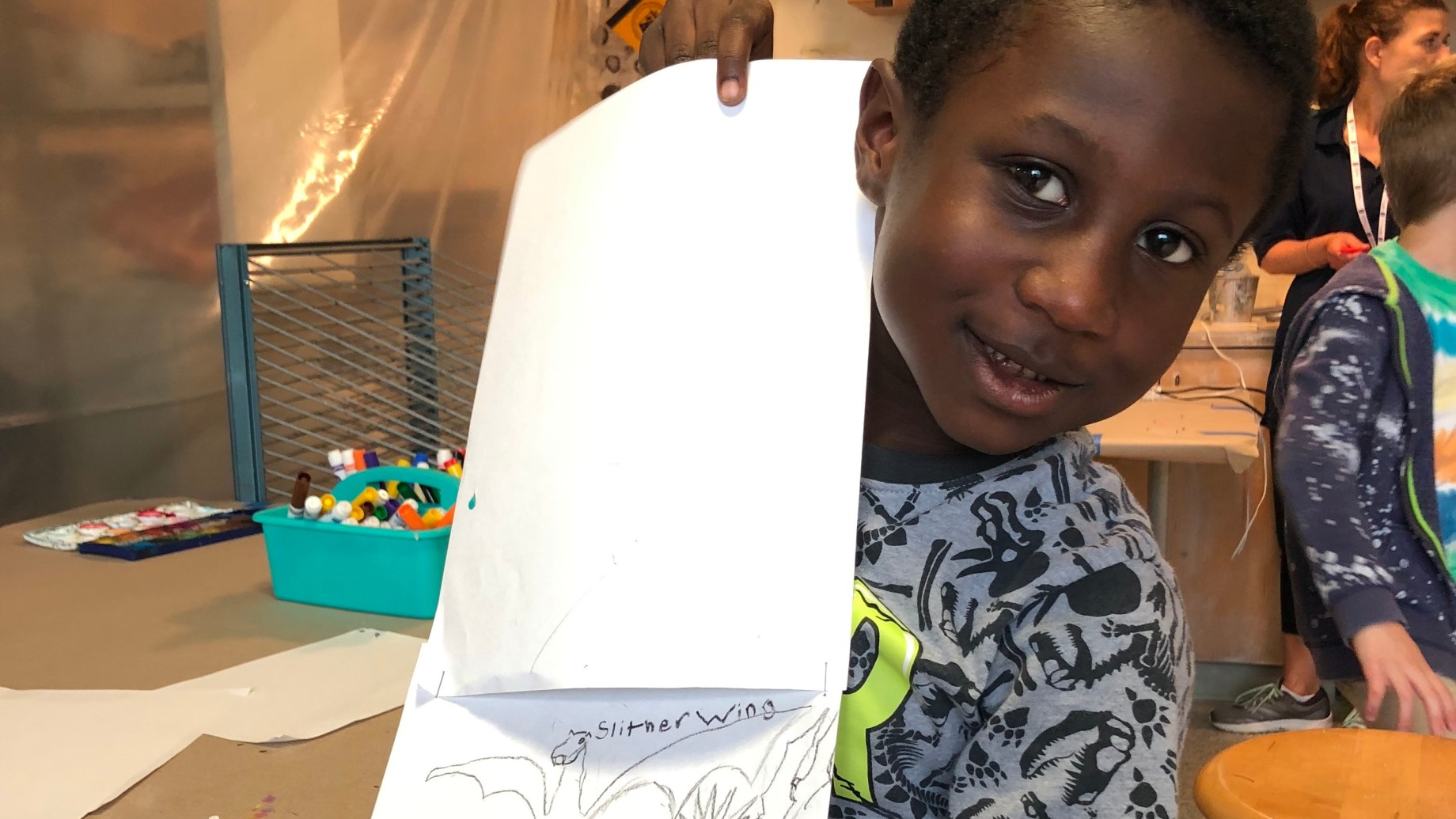 A child showing his drawing