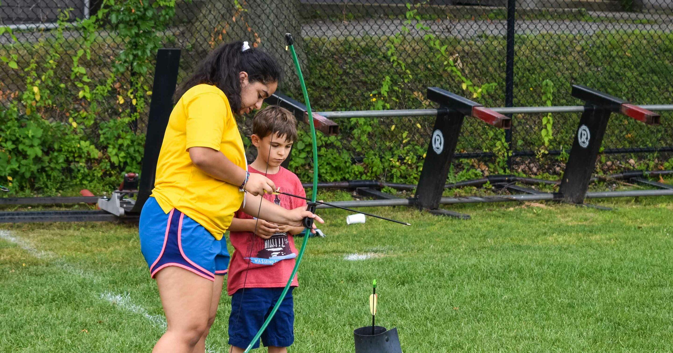 Staff teaching camper archery