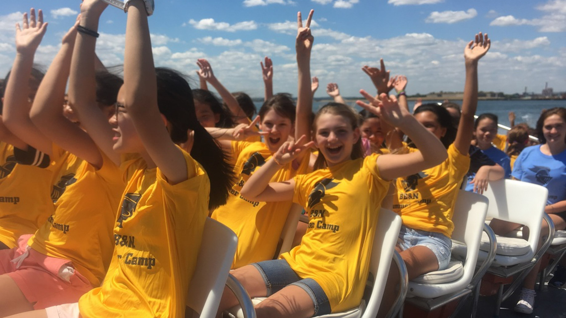 summer campers on boat trip with arms in the air