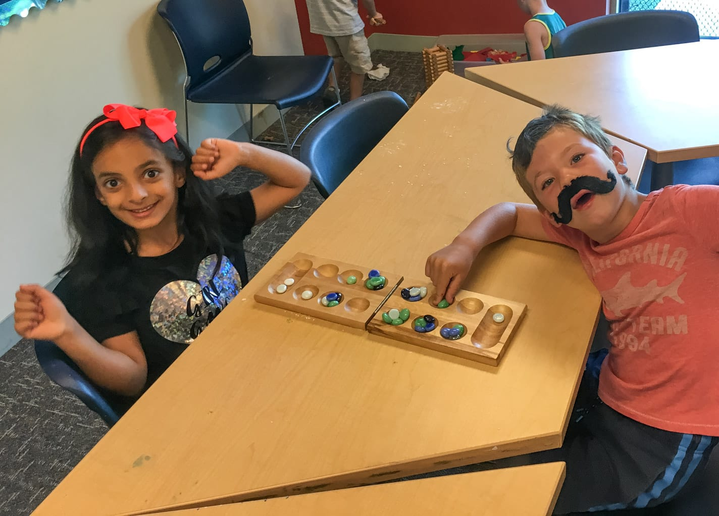 Kids playing mancala indoors