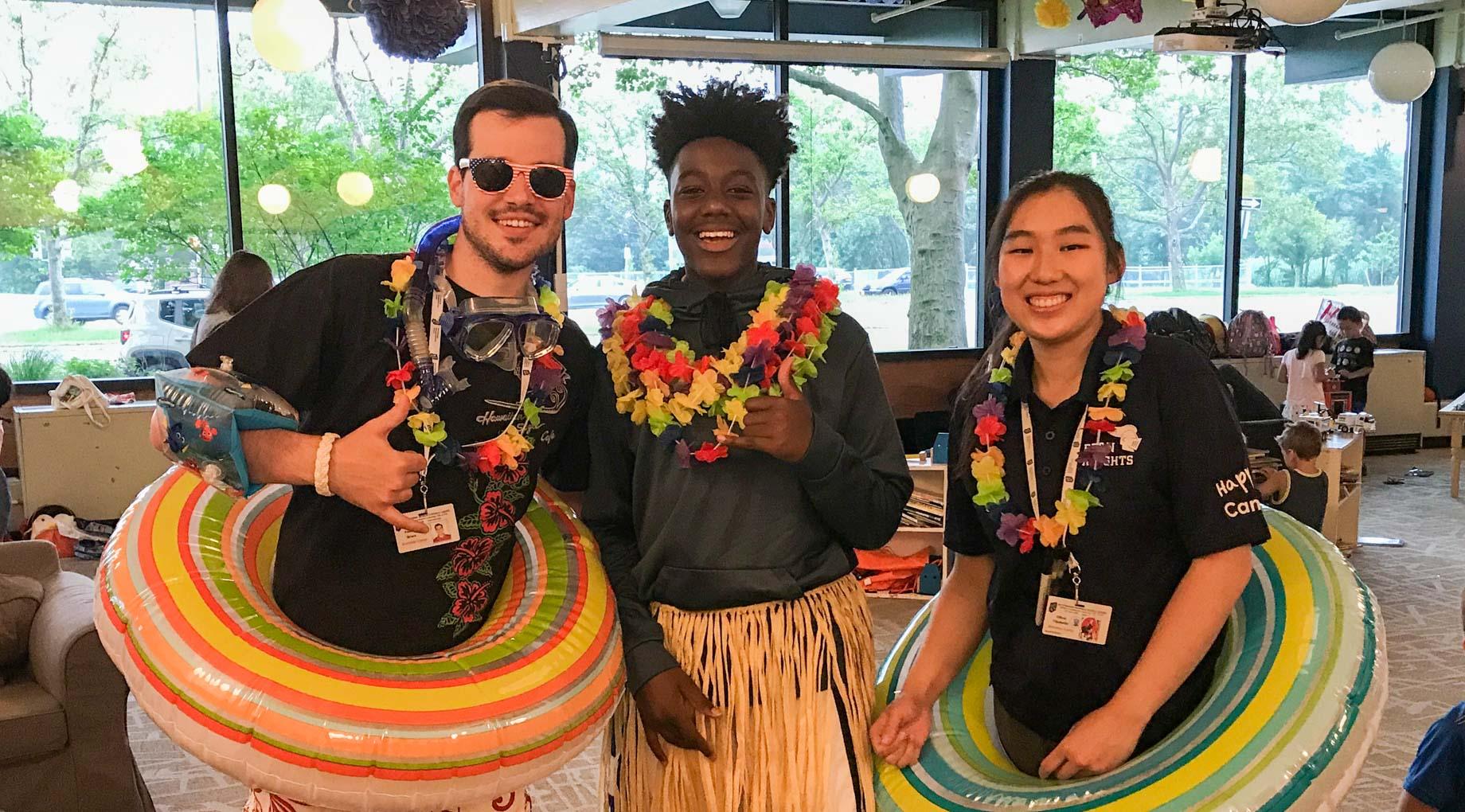 Three staff wearing Hawaiian outfits